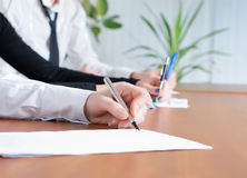 La main de la personne signant un document Photos stock
