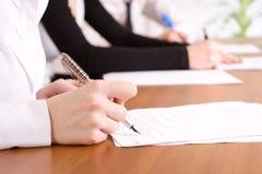 La main de la personne signant un document important Images stock