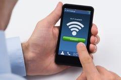 La main de la personne tenant le téléphone portable avec le signal de WiFi image stock