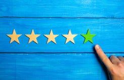 La main de mâle indique la cinquième étoile verte sur un fond en bois bleu Cinq étoiles Estimation de restaurant ou d'hôtel, appl Images stock