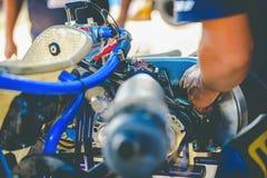 La main de mécanicien vont kart emballant le contrôle de service du ` s de moteur l'avai photographie stock