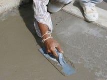 La main de maçon finit un plancher en béton nouvellement versé image libre de droits