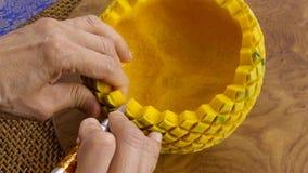 La main de Madame ouvrant le potiron dans un modèle floral Type thaï photo stock