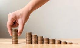 La main de masculin ou la femelle mettant des pièces de monnaie empilent la croissance croissante s d'étape Photographie stock libre de droits