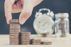 La main de la pile de mise masculine ou femelle de pièce de monnaie intensifient des économies d'augmentation Image libre de droits