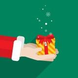 La main de Santa Claus deux donnent à cadeau le Joyeux Noël Illustration Stock