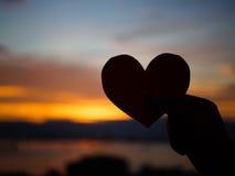 La main de silhouette soulève le coeur de papier rouge avec la lumière du soleil de tache floue pendant le coucher du soleil, Photos libres de droits