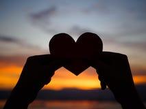 La main de silhouette soulève le coeur de papier rouge avec la lumière du soleil de tache floue pendant le coucher du soleil, Images stock