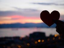La main de silhouette soulève le coeur de papier rouge avec la lumière du soleil de tache floue pendant le coucher du soleil, Photographie stock libre de droits