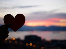 La main de silhouette soulève le coeur de papier rouge avec la lumière du soleil de tache floue pendant le coucher du soleil, Photo libre de droits
