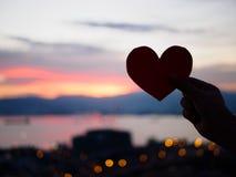 La main de silhouette soulève le coeur de papier rouge avec la lumière du soleil de tache floue pendant le coucher du soleil, Image stock