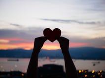 La main de silhouette soulève le coeur de papier rouge avec la lumière du soleil de tache floue pendant le coucher du soleil Image stock