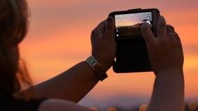 La main de silhouette tenant le smartphone prennent la photo au coucher du soleil et évasent lumière banque de vidéos