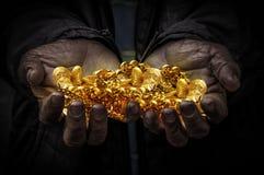 La main de travailleurs portent l'or Photographie stock