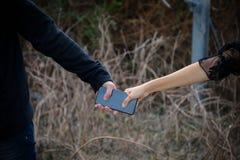 la main de voleur volent le smartphone de la fille Images libres de droits