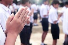 La main des étudiants payent le respect au Bouddha photo stock