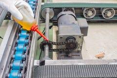 La main des baisses d'huile de graissage de technicien à la commande à chaînes pour l'entretien image stock