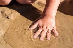 La main des enfants se situant dans l'eau sur le sable Photographie stock libre de droits