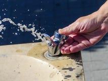 La main des femmes caucasiennes ouvre le robinet d'eau, photographie stock libre de droits
