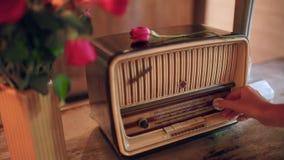 La main des femmes inclut la radio La fleur de Rose se trouve sur le récepteur vintage et r?tro banque de vidéos