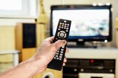 La main des hommes envoie l'à télécommande à la TV Images stock