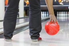 La main des hommes jette la boule de bowling sur des plans rapprochés de goupilles de bowling photo stock