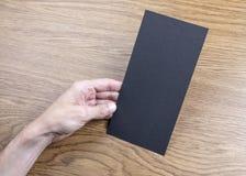 La main des hommes tenant l'insecte noir photo stock