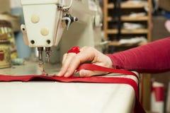 La main des ouvrières couturières sur le tissu rouge et le ruban passant en cousant le mA Photo libre de droits