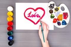 La main dessine le coeur sur la feuille Image stock