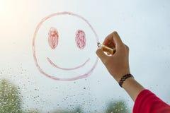 La main dessine un smiley positif sur une fenêtre pluvieuse d'automne images stock