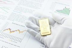La main droite d'homme avec un gant pratique blanc est la représentation/présentant une barre d'or d'une once à un client Photographie stock