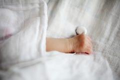 La main du bébé nouveau-né prenant l'écouteur Photographie stock libre de droits