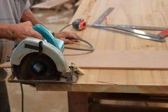 La main du bois de coupe de travailleur avec le cercle électrique a vu Image stock