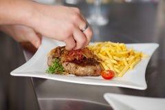 La main du chef garnissant le plat au comptoir de cuisine Photographie stock