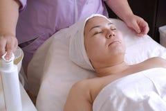 La main du cosmetologist dans le premier plan mouille un tissu dans une lotion de nettoyage La procédure pour rajeunir le ski des photos libres de droits