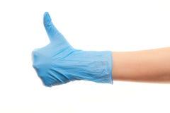 La main du docteur dans le gant chirurgical bleu montrant des pouces lèvent le signe Images libres de droits