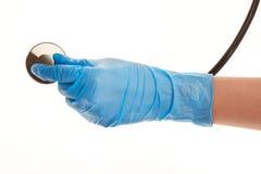 La main du docteur féminin dans le bleu a stérilisé le gant chirurgical avec le stéthoscope Photographie stock