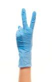 La main du docteur féminin dans le gant chirurgical bleu montrant le signe de victoire Photographie stock