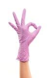 La main du docteur féminin dans le gant chirurgical pourpre montrant le signe CORRECT Photos stock