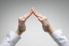 La main du femme affichant le symbole de toit Photographie stock