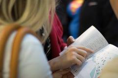 La main du femme affichant sur une carte Image stock