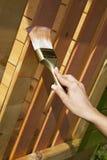 La main du femme avec le balai peignant la terrasse en bois photos libres de droits