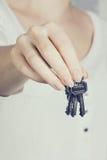 La main du femme retenant des clés neuves Image libre de droits
