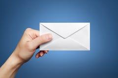 La main du femme retenant l'enveloppe fermée Image stock