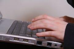 La main du femme sur les clés de l'ordinateur portatif Image stock