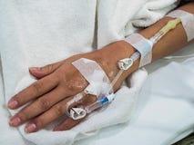 La main du patient avec l'intravenous salin (iv) Image stock