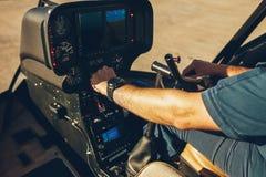 La main du pilote sur un tableau de bord d'hélicoptère Image libre de droits