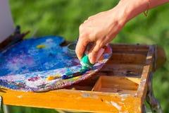 La main du ` s d'artiste, qui serre la peinture à l'huile du tube dedans Image libre de droits