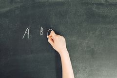 La main du ` s d'enfant avec la craie écrivent l'alphabet sur le tableau noir Image stock