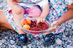 La main du ` s d'enfant prend les baies et les fruits frais Image libre de droits